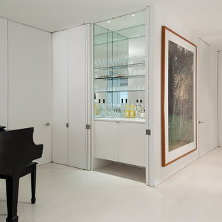 Example of a small minimalist single-wall home bar design in DC Metro with flat-panel cabinets, white cabinets, mirror backsplash and white countertops