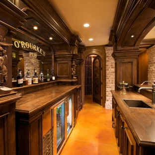 Elegant galley concrete floor seated home bar photo in Minneapolis with a drop-in sink, recessed-panel cabinets, dark wood cabinets, wood countertops and brown countertops