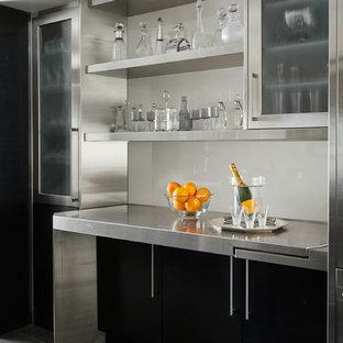 Inredning av en modern linjär hemmabar, med öppna hyllor, bänkskiva i rostfritt stål, vitt stänkskydd, glaspanel som stänkskydd och svart golv