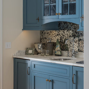 Inspiration for a small nautical galley wet bar in Portland Maine with a submerged sink, beaded cabinets, blue cabinets, marble worktops, mirror splashback, light hardwood flooring and beige floors.