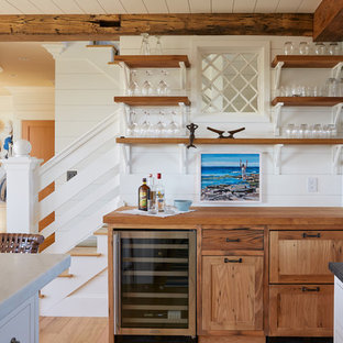 Coastal single-wall home bar photo in Portland Maine with no sink, shaker cabinets, medium tone wood cabinets, wood countertops and white backsplash