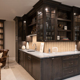 Design ideas for a medium sized traditional l-shaped wet bar in Minneapolis with a submerged sink, glass-front cabinets, dark wood cabinets, marble worktops, beige splashback, wood splashback, carpet, beige floors and grey worktops.