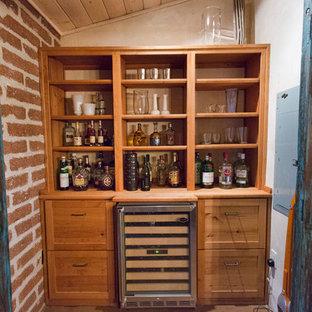 フェニックスの小さいサンタフェスタイルのおしゃれなウェット バー (I型、オープンシェルフ、淡色木目調キャビネット、木材カウンター、コンクリートの床) の写真