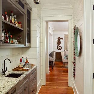 チャールストンのトロピカルスタイルのおしゃれなウェット バー (無垢フローリング、I型、アンダーカウンターシンク、落し込みパネル扉のキャビネット、グレーのキャビネット、白いキッチンパネル、茶色い床) の写真