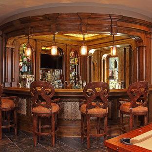 ミネアポリスの広いラスティックスタイルのおしゃれな着席型バー (コの字型、濃色木目調キャビネット、木材カウンター、セラミックタイルの床) の写真