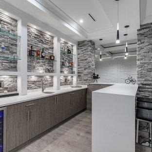 バンクーバーの中くらいのコンテンポラリースタイルのおしゃれなウェット バー (コの字型、アンダーカウンターシンク、フラットパネル扉のキャビネット、グレーのキャビネット、淡色無垢フローリング、グレーの床、人工大理石カウンター、グレーのキッチンパネル、石タイルのキッチンパネル、白いキッチンカウンター) の写真
