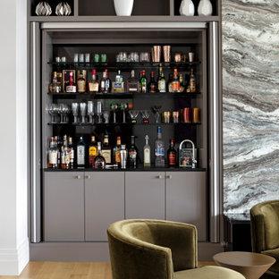 ボルチモアの中くらいのコンテンポラリースタイルのおしゃれなウェット バー (I型、一体型シンク、グレーのキャビネット、グレーのキッチンパネル、淡色無垢フローリング、茶色い床、黒いキッチンカウンター) の写真