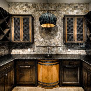 オースティンの広いラスティックスタイルのおしゃれなウェット バー (コの字型、アンダーカウンターシンク、落し込みパネル扉のキャビネット、濃色木目調キャビネット、クオーツストーンカウンター、茶色いキッチンパネル、石タイルのキッチンパネル、トラバーチンの床、茶色い床) の写真