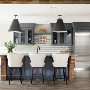 Large transitional galley ceramic floor and brown floor wet bar photo in Minneapolis with recessed-panel cabinets, gray cabinets, gray backsplash and gray countertops