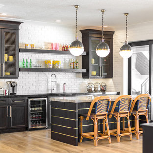ソルトレイクシティの広いトランジショナルスタイルのおしゃれな着席型バー (シェーカースタイル扉のキャビネット、白いキッチンパネル、淡色無垢フローリング、アンダーカウンターシンク、黒いキャビネット、大理石カウンター、サブウェイタイルのキッチンパネル、茶色い床、白いキッチンカウンター) の写真