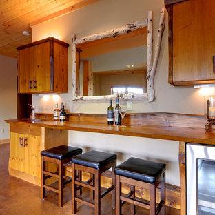 Esempio di un bancone bar rustico di medie dimensioni con pavimento in cemento, ante lisce, ante in legno scuro, top in legno e top marrone