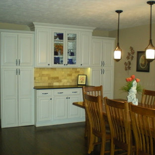 Design ideas for a small classic single-wall wet bar in Orange County with raised-panel cabinets, white cabinets, beige splashback, stone tiled splashback, dark hardwood flooring and brown floors.