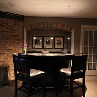 Foto di un bancone bar chic di medie dimensioni con moquette, lavello da incasso, ante nere, top in vetro e pavimento beige