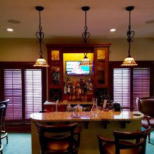 Idee per un piccolo angolo bar con lavandino classico con lavello sottopiano, ante di vetro, ante in legno scuro, top in granito, moquette e pavimento verde