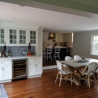 ニューヨークの小さいトランジショナルスタイルのおしゃれなウェット バー (I型、シンクなし、ガラス扉のキャビネット、白いキャビネット、クオーツストーンカウンター、マルチカラーのキッチンパネル、セメントタイルのキッチンパネル、無垢フローリング、茶色い床、白いキッチンカウンター) の写真