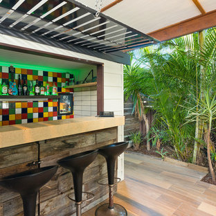 This is an example of a beach style seated home bar in Gold Coast - Tweed with multi-coloured splashback, beige floor, beige benchtop and mosaic tile splashback.