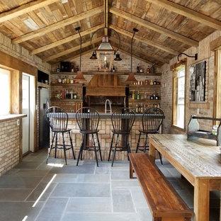 Rustic galley wet bar in Milwaukee with open cabinets, medium wood cabinets, concrete worktops, brick splashback, slate flooring and grey floors.