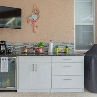 Immagine di un piccolo angolo bar con lavandino tradizionale con lavello sottopiano, ante in stile shaker, ante bianche, top in granito, paraspruzzi grigio, paraspruzzi in ardesia, pavimento in cemento, pavimento beige e top grigio