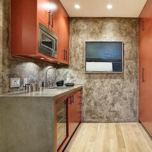 Foto di un piccolo angolo bar design con ante lisce, parquet chiaro, pavimento beige, lavello sottopiano e ante arancioni