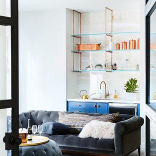 Immagine di un piccolo angolo bar con lavandino minimal con lavello sottopiano, ante lisce, ante blu, paraspruzzi beige, parquet chiaro, top in onice, paraspruzzi in lastra di pietra e top beige