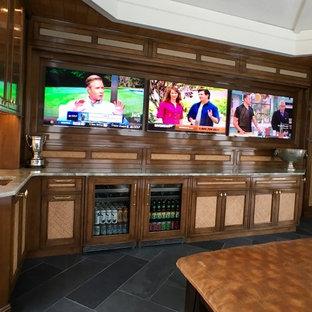 広いトラディショナルスタイルのおしゃれなウェット バー (L型、アンダーカウンターシンク、フラットパネル扉のキャビネット、中間色木目調キャビネット、珪岩カウンター、マルチカラーのキッチンパネル、木材のキッチンパネル、スレートの床) の写真
