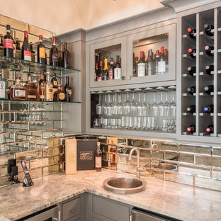 This is an example of a medium sized coastal u-shaped wet bar in Houston with a built-in sink, grey cabinets, granite worktops, mirror splashback, grey worktops and glass-front cabinets.