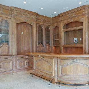 マイアミの広いトラディショナルスタイルのおしゃれな着席型バー (L型、レイズドパネル扉のキャビネット、濃色木目調キャビネット、木材カウンター、茶色いキッチンパネル、木材のキッチンパネル、ライムストーンの床、グレーの床) の写真