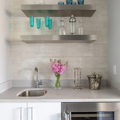 Inspiration for a small coastal single-wall wet bar remodel in Jacksonville with an undermount sink, flat-panel cabinets, white cabinets, beige backsplash and gray countertops
