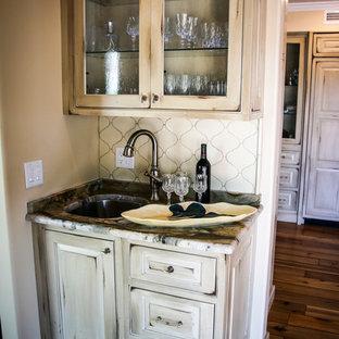 マイアミの小さいラスティックスタイルのおしゃれなウェット バー (I型、ドロップインシンク、レイズドパネル扉のキャビネット、ヴィンテージ仕上げキャビネット、大理石カウンター、白いキッチンパネル、合板フローリング、茶色い床、マルチカラーのキッチンカウンター) の写真
