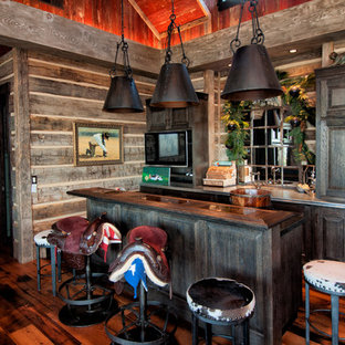Inspiration for a mid-sized rustic galley dark wood floor seated home bar remodel in Salt Lake City with raised-panel cabinets, dark wood cabinets and mirror backsplash