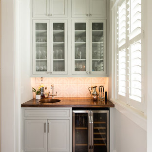 チャールストンのトラディショナルスタイルのおしゃれなウェット バー (I型、ドロップインシンク、ガラス扉のキャビネット、グレーのキャビネット、マルチカラーのキッチンパネル、濃色無垢フローリング) の写真
