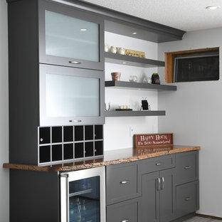 Idee per un carrello bar minimalista di medie dimensioni con ante in stile shaker, ante grigie, top in quarzite e top arancione