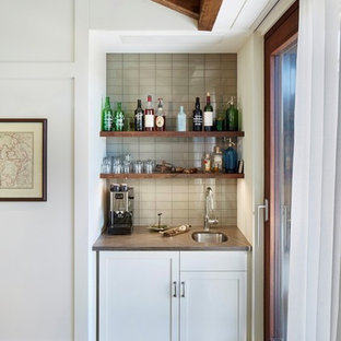 This is an example of a small traditional single-wall wet bar in New York with a submerged sink, grey splashback, light hardwood flooring, shaker cabinets, white cabinets, marble worktops, glass tiled splashback and grey worktops.