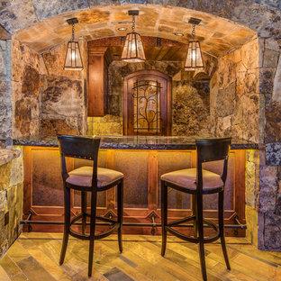 Esempio di un bancone bar stile rurale di medie dimensioni con ante con riquadro incassato, ante in legno bruno e pavimento in compensato