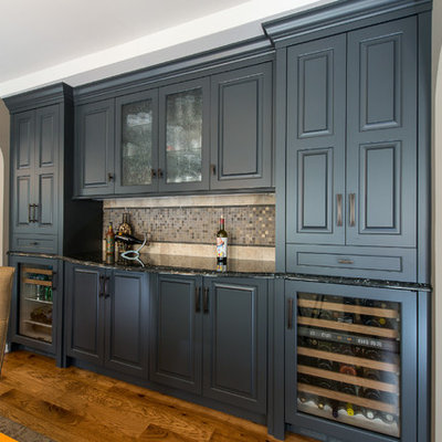 Wet bar - mid-sized contemporary single-wall medium tone wood floor and brown floor wet bar idea in Minneapolis with glass-front cabinets, gray cabinets, granite countertops, beige backsplash, stone tile backsplash and no sink
