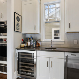 Photo of a medium sized modern galley wet bar in Atlanta with a submerged sink, shaker cabinets, white cabinets, engineered stone countertops, white splashback, glass tiled splashback, dark hardwood flooring, brown floors and grey worktops.