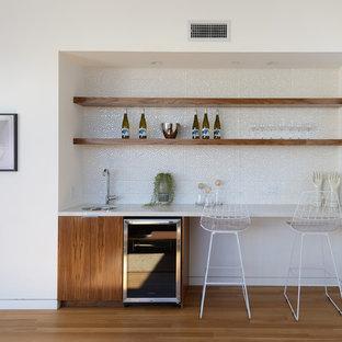 Modern inredning av en liten linjär hemmabar med stolar, med mellanmörkt trägolv, släta luckor, skåp i mörkt trä, vitt stänkskydd och brunt golv