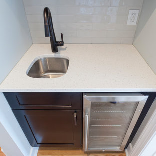 Photo of a small classic single-wall wet bar in Philadelphia with a submerged sink, shaker cabinets, dark wood cabinets, engineered stone countertops, white splashback, metro tiled splashback, light hardwood flooring, brown floors and white worktops.