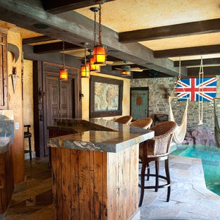 Seated home bar - mid-sized rustic l-shaped slate floor and brown floor seated home bar idea in Phoenix with an undermount sink, stone slab backsplash, raised-panel cabinets, distressed cabinets, onyx countertops and gray backsplash