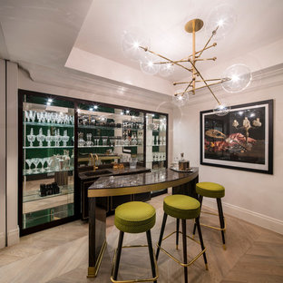 Contemporary single-wall wet bar in London with black cabinets, light hardwood flooring, brown floors and mirror splashback.