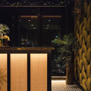 Foto di un piccolo angolo bar bohémian con ante con riquadro incassato, ante nere, top in laminato, paraspruzzi a specchio, pavimento con piastrelle in ceramica, pavimento nero e top nero