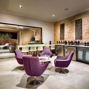 フェニックスの広いサンタフェスタイルのおしゃれな着席型バー (I型、ガラス扉のキャビネット、グレーのキャビネット、ベージュキッチンパネル、ライムストーンのキッチンパネル、磁器タイルの床、グレーの床、白いキッチンカウンター) の写真