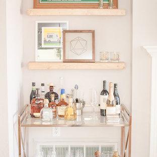 Imagen de bar en casa con carrito de bar bohemio, de tamaño medio, con suelo laminado y suelo marrón