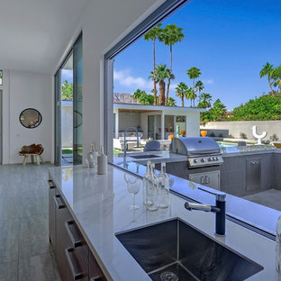 Photo of a medium sized modern single-wall wet bar in Los Angeles with a submerged sink, flat-panel cabinets, dark wood cabinets, marble worktops, concrete flooring, grey floors and white worktops.