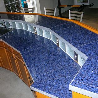他の地域の中サイズのエクレクティックスタイルのおしゃれな着席型バー (ll型、再生ガラスカウンター、コンクリートの床、茶色い床) の写真