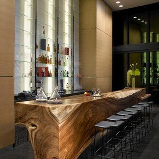 マイアミの巨大なモダンスタイルのおしゃれな着席型バー (ll型、オープンシェルフ、木材カウンター、白いキッチンパネル、ガラス板のキッチンパネル、グレーの床、茶色いキッチンカウンター) の写真