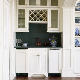 This is an example of a medium sized traditional single-wall wet bar in Providence with white cabinets, glass-front cabinets, green splashback, brown floors and dark hardwood flooring.