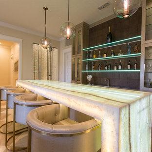 Foto di un grande bancone bar design con lavello sottopiano, ante di vetro, ante beige, top in onice, paraspruzzi marrone e top bianco