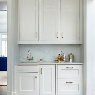 Photo of a small traditional single-wall wet bar in New York with shaker cabinets, white cabinets, marble worktops, white splashback, marble splashback, medium hardwood flooring, brown floors and white worktops.