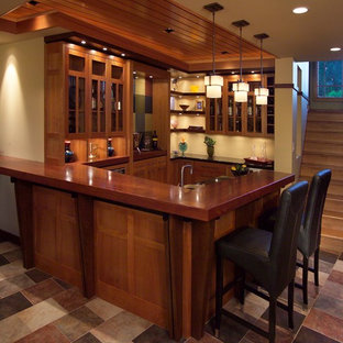 Example of a mid-sized arts and crafts u-shaped ceramic floor and multicolored floor seated home bar design in Minneapolis with glass-front cabinets, medium tone wood cabinets, wood countertops and brown countertops